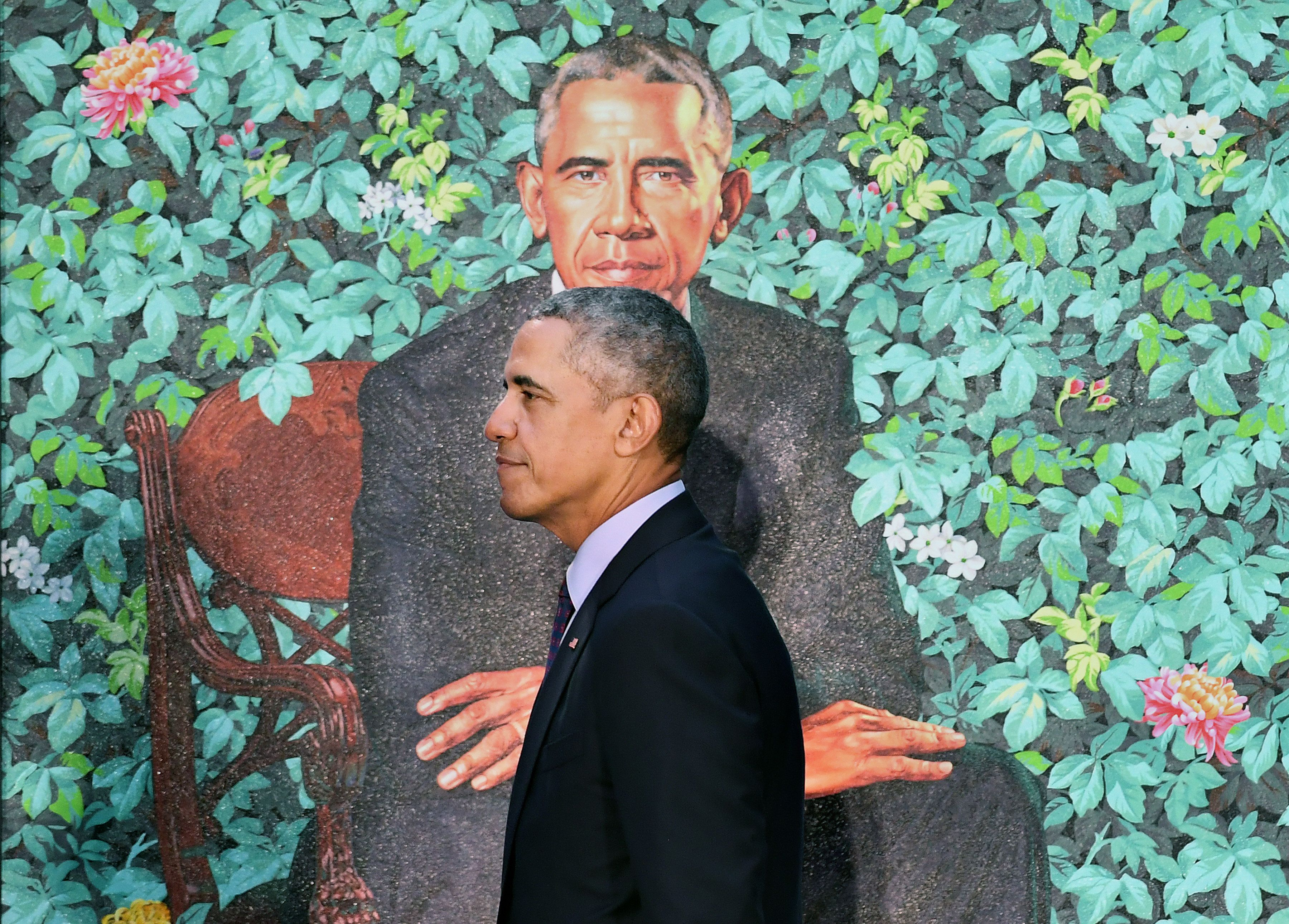 WASHINGTON, DC - FEBRUARY 12: Former President Barack Obama walks by his presidential portrait as he and former First Lady Michelle Obama have their portraits unveiled at the Smithsonian National Portrait Gallery on Monday February 12, 2018 in Washington, DC. The former President's portrait was painted by Kehinde Wiley while the former First Lady's portrait was painted by Amy Sherald. (Photo by Matt McClain/The Washington Post via Getty Images)