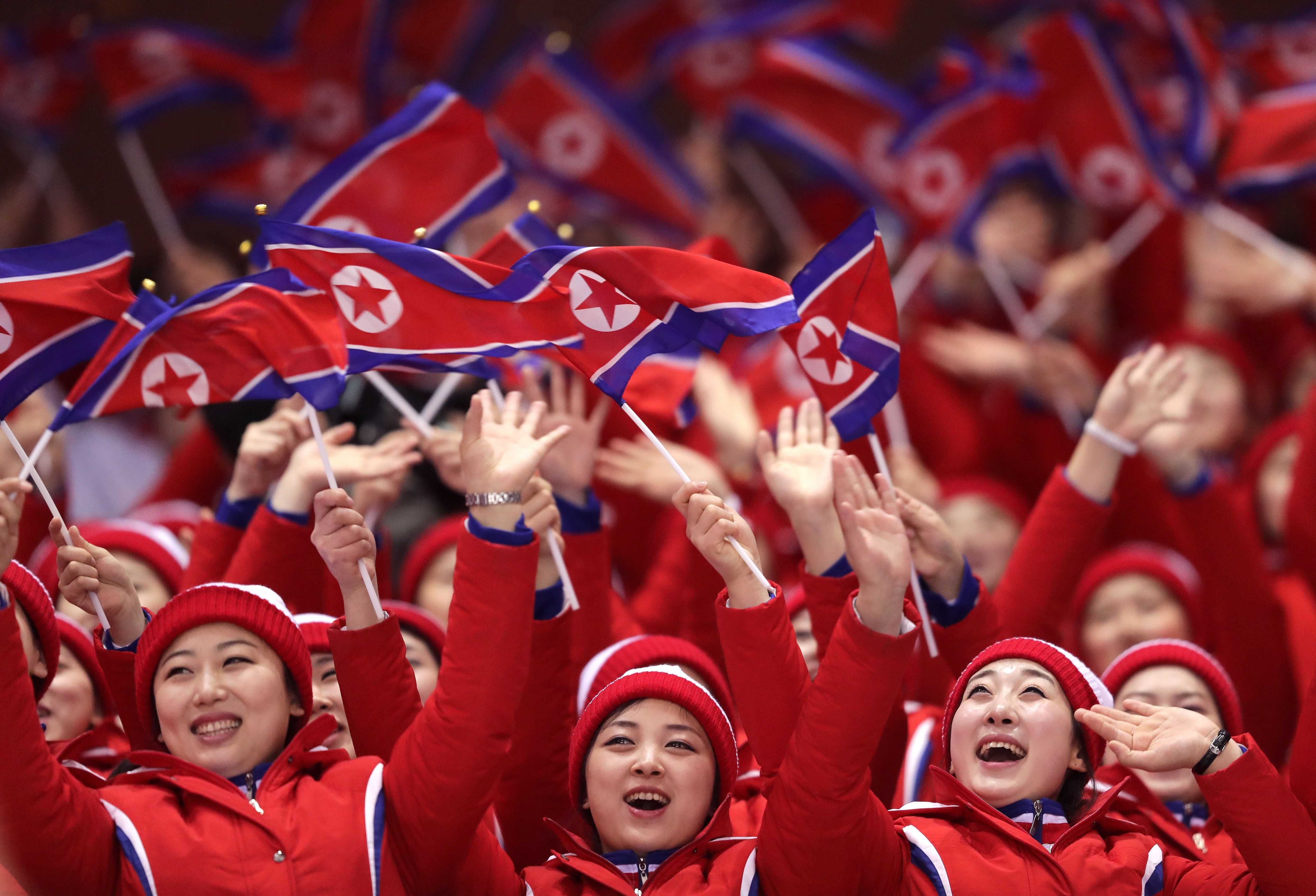 GANGNEUNG, SOUTH KOREA - FEBRUARY 14:  North Korean cheerleaders wave flags during the Pair Skating Short Program on day five of the PyeongChang 2018 Winter Olympics at Gangneung Ice Arena on February 14, 2018 in Gangneung, South Korea.  (Photo by Richard Heathcote/Getty Images)