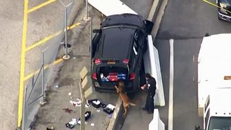 A K9 inspects an SUV after it appears to have crashed into barricades outside of the NSAs headquarters in Maryland