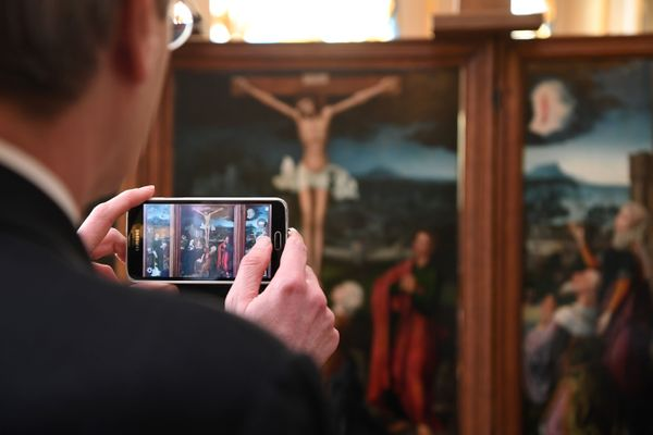 "A man takes a picture of ""Triptych of the Crucifixion,"" which is attributed to Flemish painter Joachim Patinir."