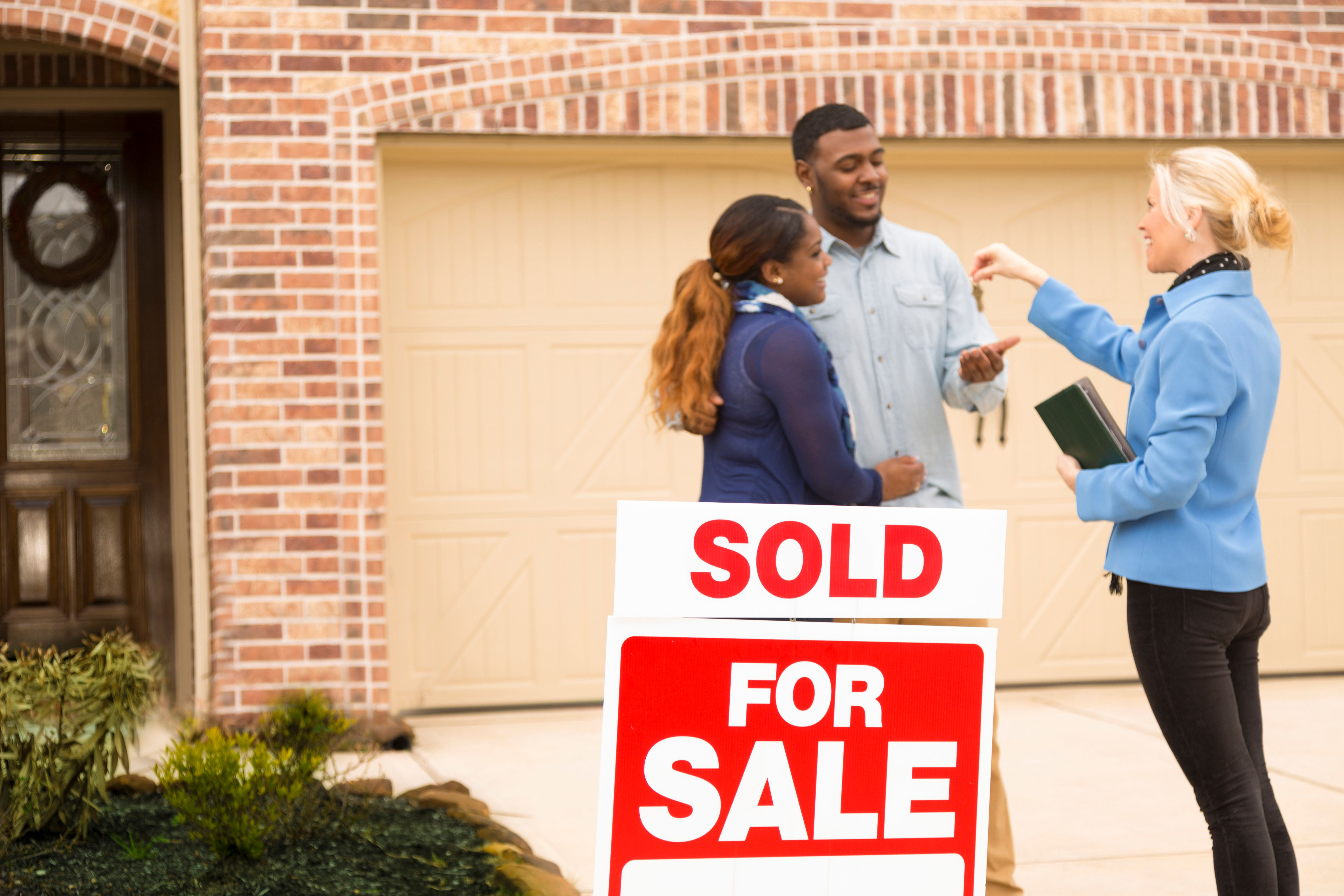 Excited African descent couple receives the keys to their first home real estate purchase from realtor.  The happy young adults stand in front of brick home.