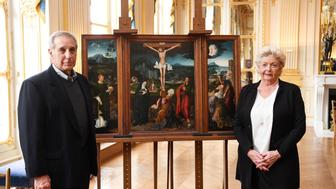 Henrietta Schubert (R) and Christopher Bromberg (L), right holders and grandchildren of Henry and Hertha Bromberg, pose on February 12, 2018 at the Culture Ministry in Paris, next to a Triptych of the Crucifixion attributed to Flemish painter Joachim Patenier.