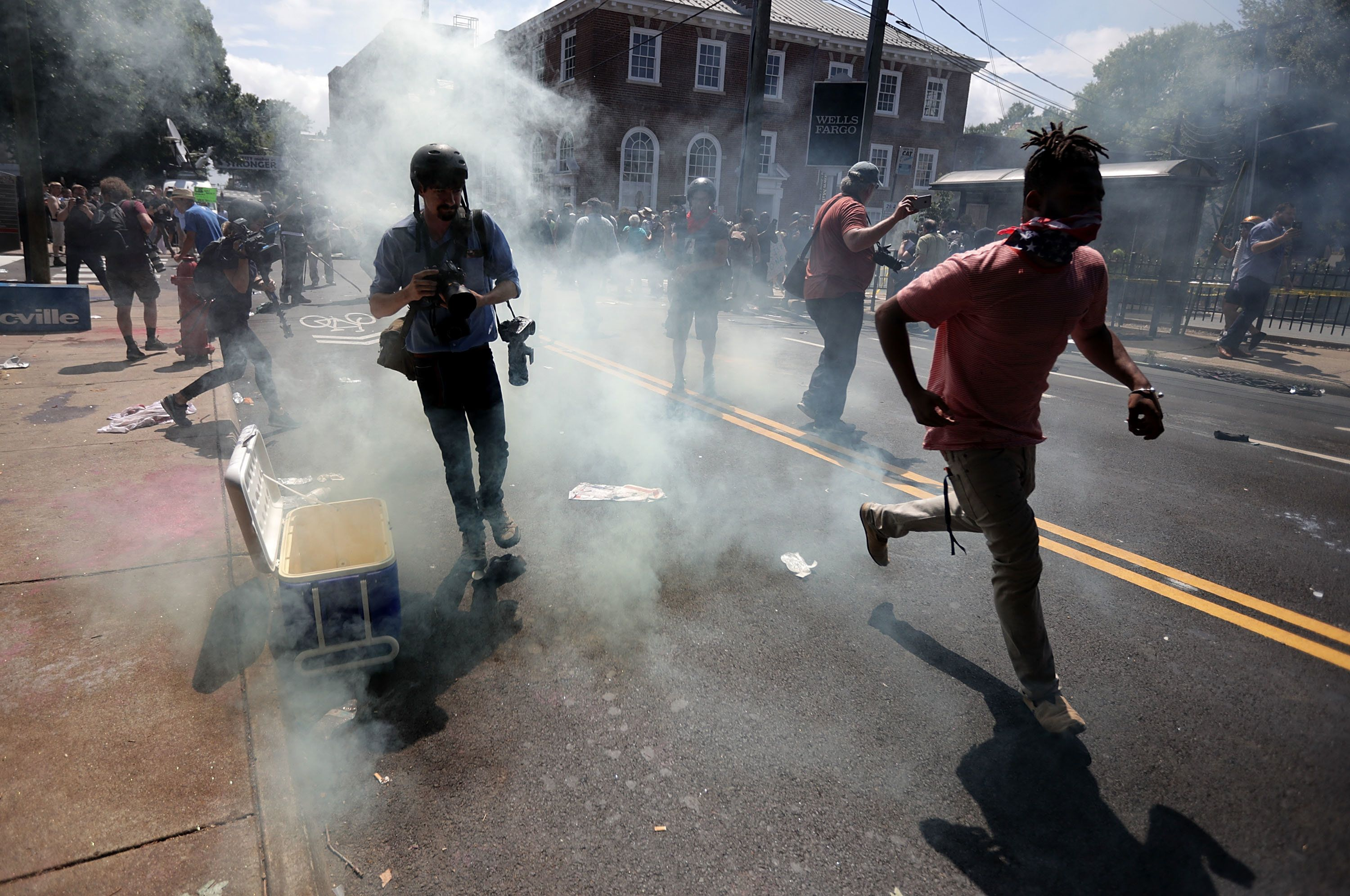 CHARLOTTESVILLE, VA - AUGUST 12:  Protesters and journalists pull back after tear gas was used on the outskirts of Emancipation Park during the Unite the Right rally August 12, 2017 in Charlottesville, Virginia. After clashes with anti-facist protesters and police the rally was declared an unlawful gathering and people were forced out of Lee Park, where a statue of Confederate General Robert E. Lee is slated to be removed.  (Photo by Chip Somodevilla/Getty Images)