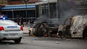 BALTIMORE, MD - APRIL 27:  A Baltimore Police car passes two cars on fire near the intersection of Pennsylvania Avenue and North Avenue , April 27, 2015 in Baltimore, Maryland. Riots have erupted in Baltimore following the funeral service for Freddie Gray, who died last week while in Baltimore Police custody. (Photo by Drew Angerer/Getty Images)