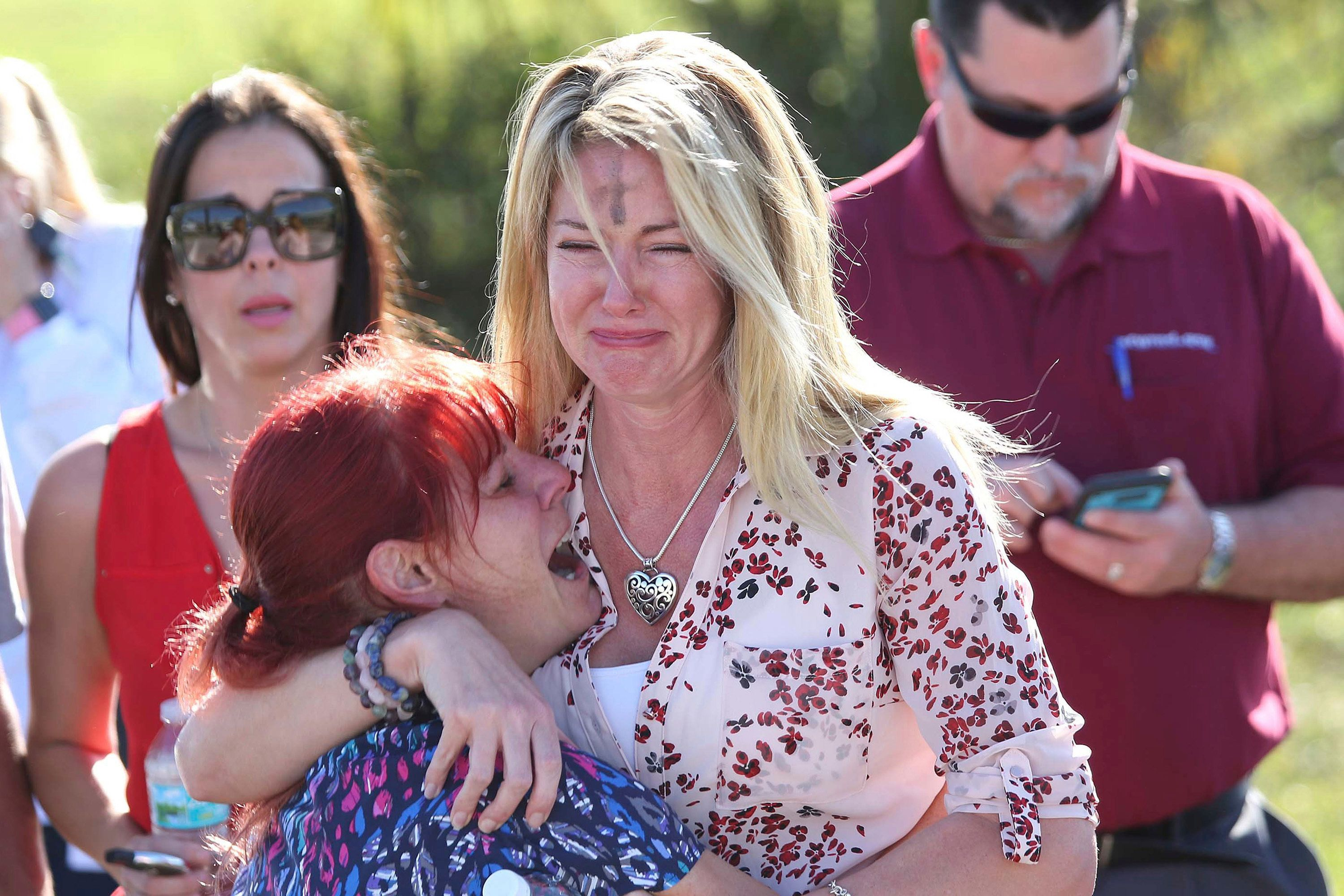 Parents wait for news after reports of a shooting at Marjory Stoneman Douglas High School in Parkland, Fla., on Wednesday. One woman, seen sobbing, had a cross marked on her forehead with it being Ash Wednesday.