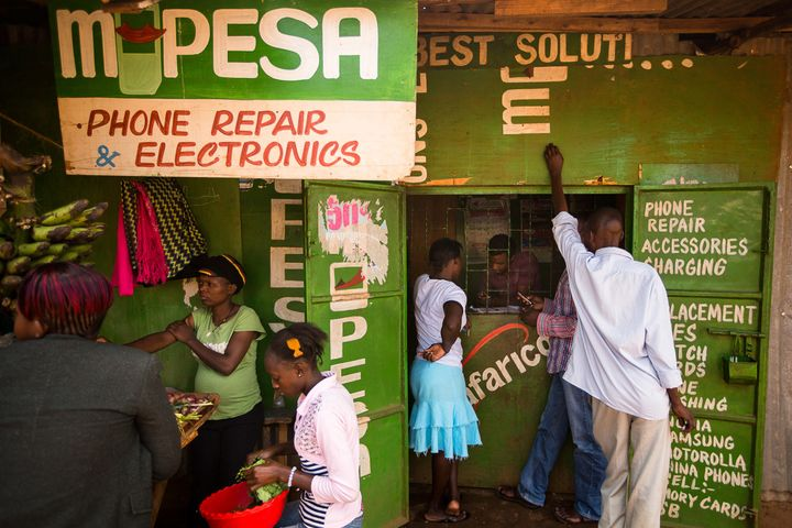 Residents transfer money using the M-Pesa banking service at a store in Nairobi, Kenya.