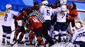 TOPSHOT - Players pile up on the Canadian goal in the women's preliminary round ice hockey match between the US and Canada during the Pyeongchang 2018 Winter Olympic Games at the Kwandong Hockey Centre in Gangneung on February 15, 2018.   / AFP PHOTO / Brendan Smialowski        (Photo credit should read BRENDAN SMIALOWSKI/AFP/Getty Images)