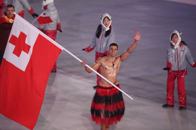 Flag bearer Pita Taufatofua of Tonga leads the team as they parade around the arena during the opening