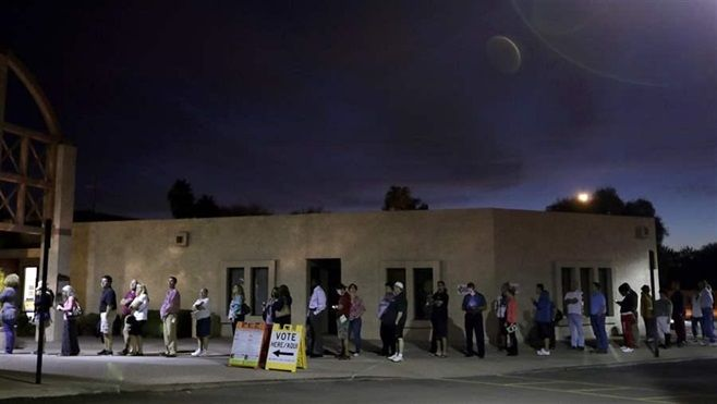 Voters in Phoenix, seen here waiting for polls to open at dawn in November 2016, had to wait as long as four hours to vote du