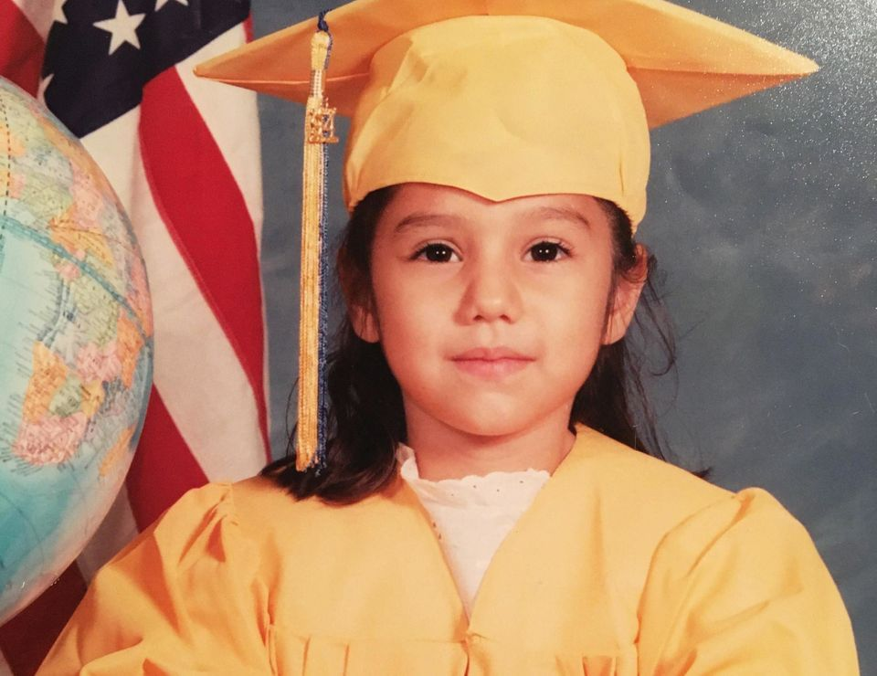 Norma, age 5, poses for her kindergarten graduation