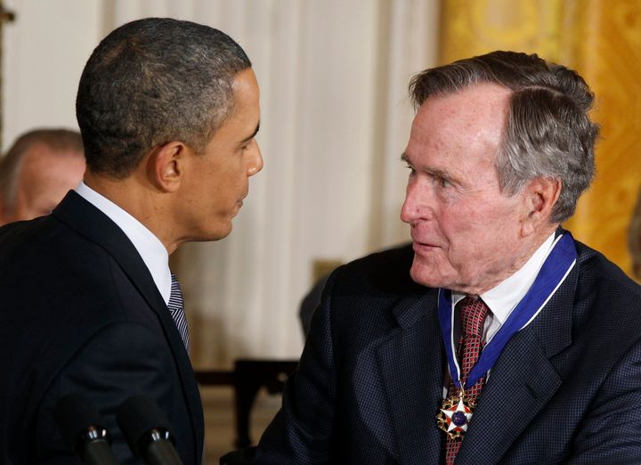 U.S. President Barack Obama congratulates Medal of Freedom recipient and former U.S. President George H.W. Bush during a cere
