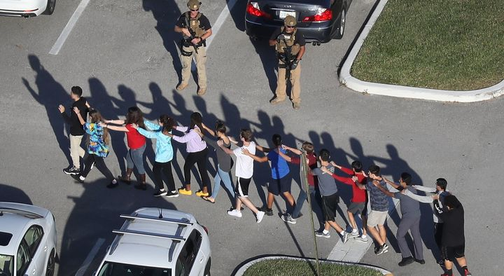 Students evacuate Marjory Stoneman Douglas High School, in Parkland, Florida, after a shooting there killed nu