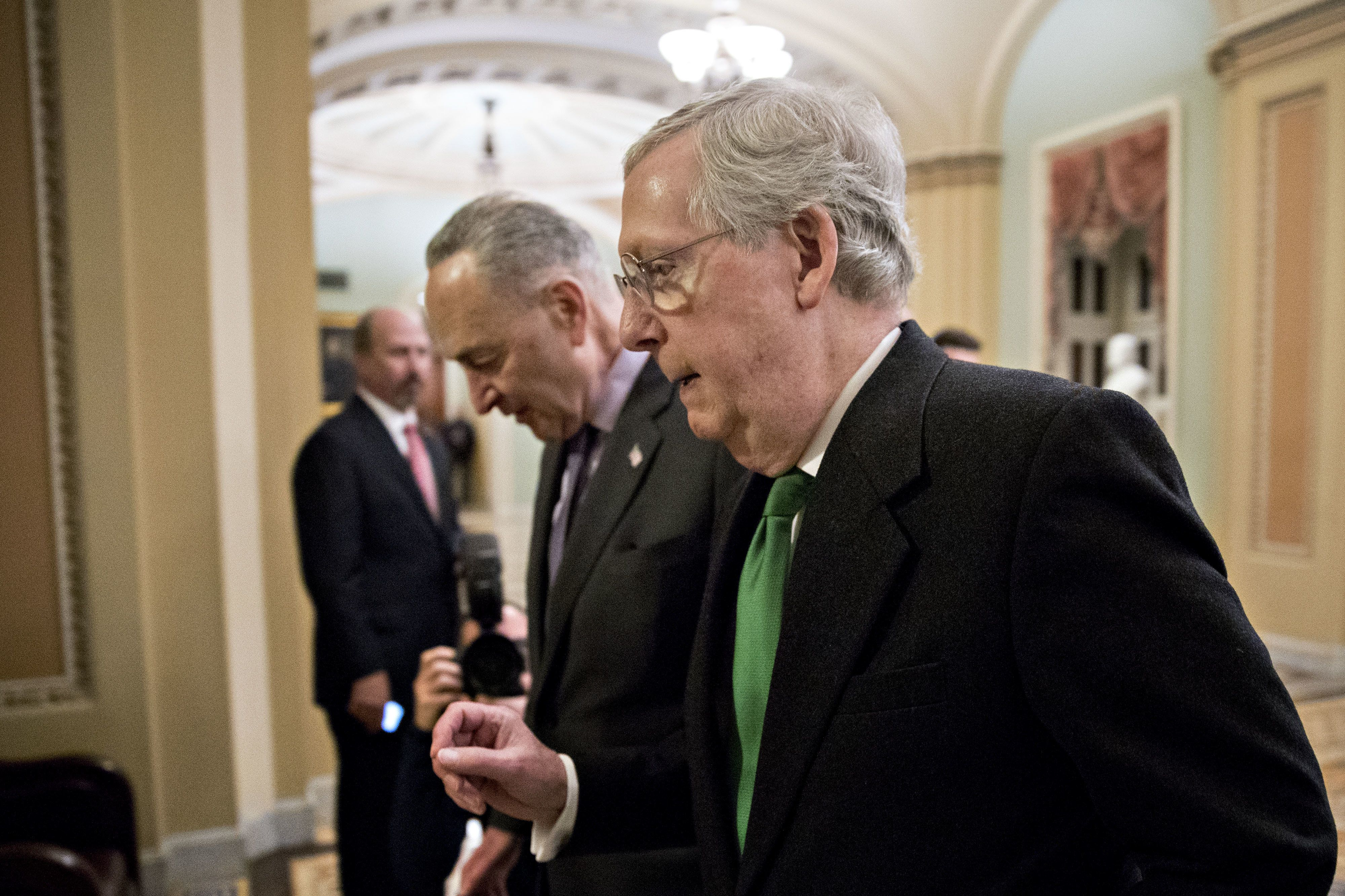 Senate Majority Leader Mitch McConnell, a Republican from Kentucky, right, talks to Senate Minority Leader Chuck Schumer, a Democrat from New York, while walking towards the Senate Chamber at the U.S. Capitol in Washington, D.C., U.S., on Wednesday, Feb. 7, 2018. Senate leaders agreed on a bipartisan two-year plan to increase federal spending by nearly $300 billion over two years, a pact likely to avert a government shutdown on Friday. Photographer: Andrew Harrer/Bloomberg via Getty Images
