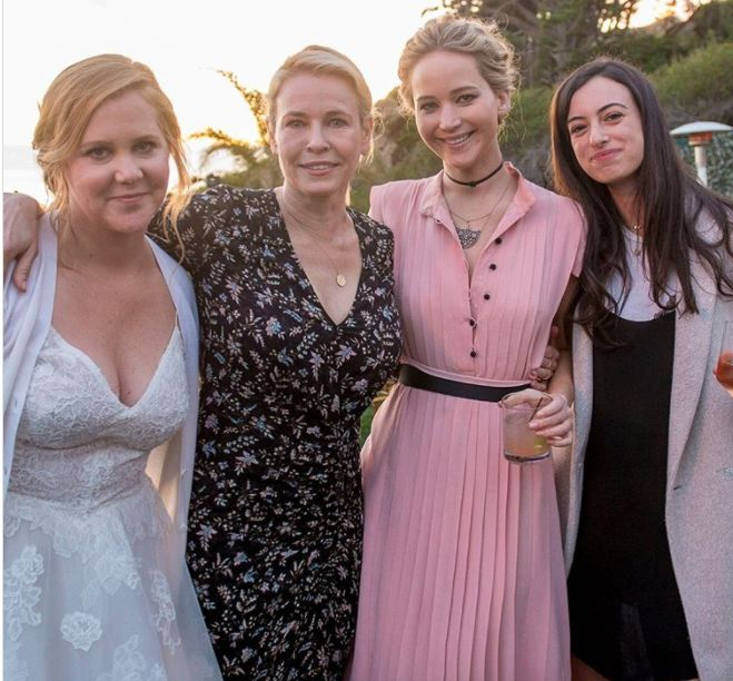 Jennifer Lawrence (second from right) had a few buttons undone at the wedding of friend Amy Schumer (left).