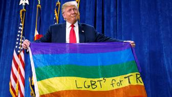 "Republican presidential nominee Donald Trump holds up a rainbow flag with ""LGBT's for TRUMP"" written on it at a campaign rally in Greeley, Colorado, U.S. October 30, 2016.   REUTERS/Carlo Allegri"