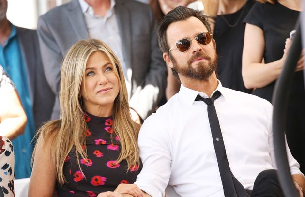 Jennifer Aniston and Justin Theroux sit together at the Hollywood Walk of Fame on July 26,