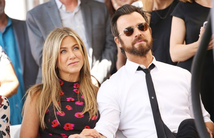 Jennifer Aniston and Justin Theroux sit together at the Hollywood Walk of Fame on July 26, 2017.