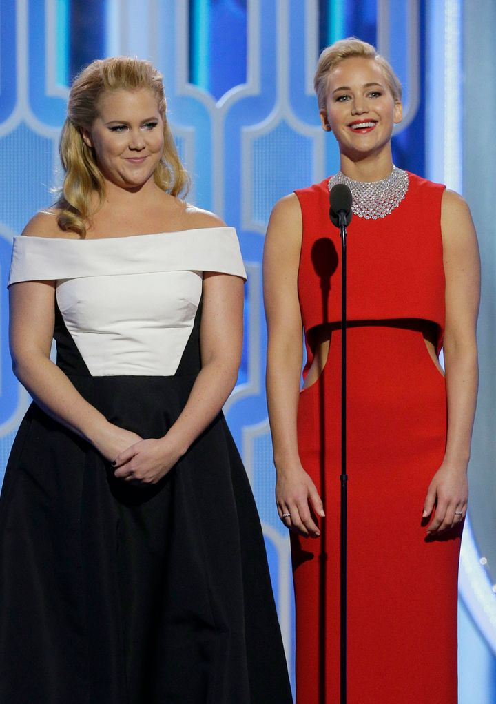 Amy Schumer and Jennifer Lawrence speak onstage during the 73rd Annual Golden Globe Awards.