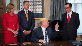 US Congresswoman Claudia Tenney (L), R-NY, and US Senator David Perdue (2nd L), R-Georgia, look on as US President Donald Trump (C) gestures at Treasury Secretary Steven Mnuchin (R) after signing financial services executive orders and memorandums at the US Treasury Department in Washington, DC, April 21, 2017. / AFP PHOTO / JIM WATSON        (Photo credit should read JIM WATSON/AFP/Getty Images)