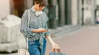 Beautiful young woman using smart phone in the city. She is standing on the street, holding shopping bags and using her smart phone. Wearing big white headphones.