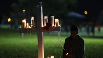 PARKLAND, FL - FEBRUARY 15:  Former Douglas student, Rachelle Borges sits near a candlelit cross during a vigil for victims of the mass shooting at Marjory Stoneman Douglas High School yesterday, at Pine Trail Park, on February 15, 2018 in Parkland, Florida. Yesterday Police arrested 19 year old former student Nikolas Cruz for killing 17 people at the high school.  (Photo by Mark Wilson/Getty Images)