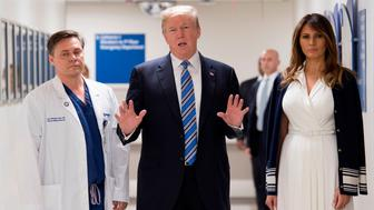 US President Donald Trump speaks with doctor Igor Nichiphorenko (L) and First Lady Melania Trump while visiting first responders at Broward Health North hospital Pompano Beach, Florida, on February 16, 2018.  US President Donald Trump and First Lady Melania Trump visited a Florida hospital to offer their respects to the victims of a mass shooting that claimed 17 lives at a nearby high school.   / AFP PHOTO / JIM WATSON        (Photo credit should read JIM WATSON/AFP/Getty Images)