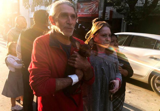 지진 발생 직후 멕시코시티 Roma 지역의 한 건물에서 대피한 한 남성이 반려견과 함께 거리를 걸어가는 모습.