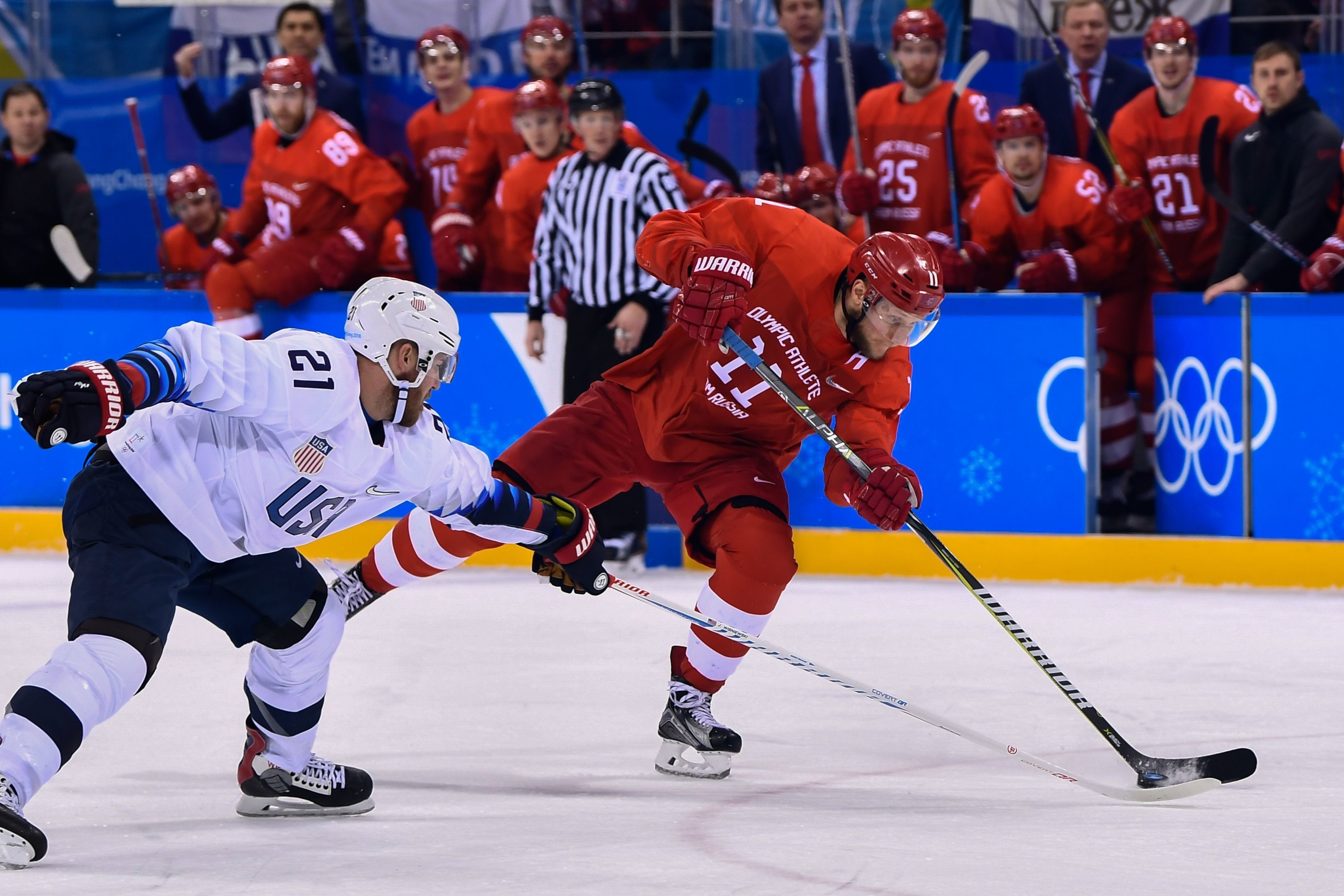 James Wisniewski and Sergei Andronov fight for the puck inSaturday's hockey match between the U.S. and the Olympic Athl