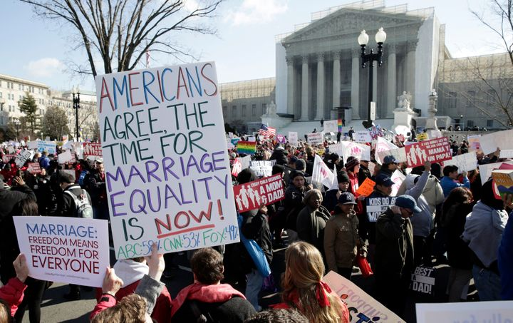 Demonstrators gather in front of the Supreme Court on March 26, 2013,before the court struck down a key provision of th
