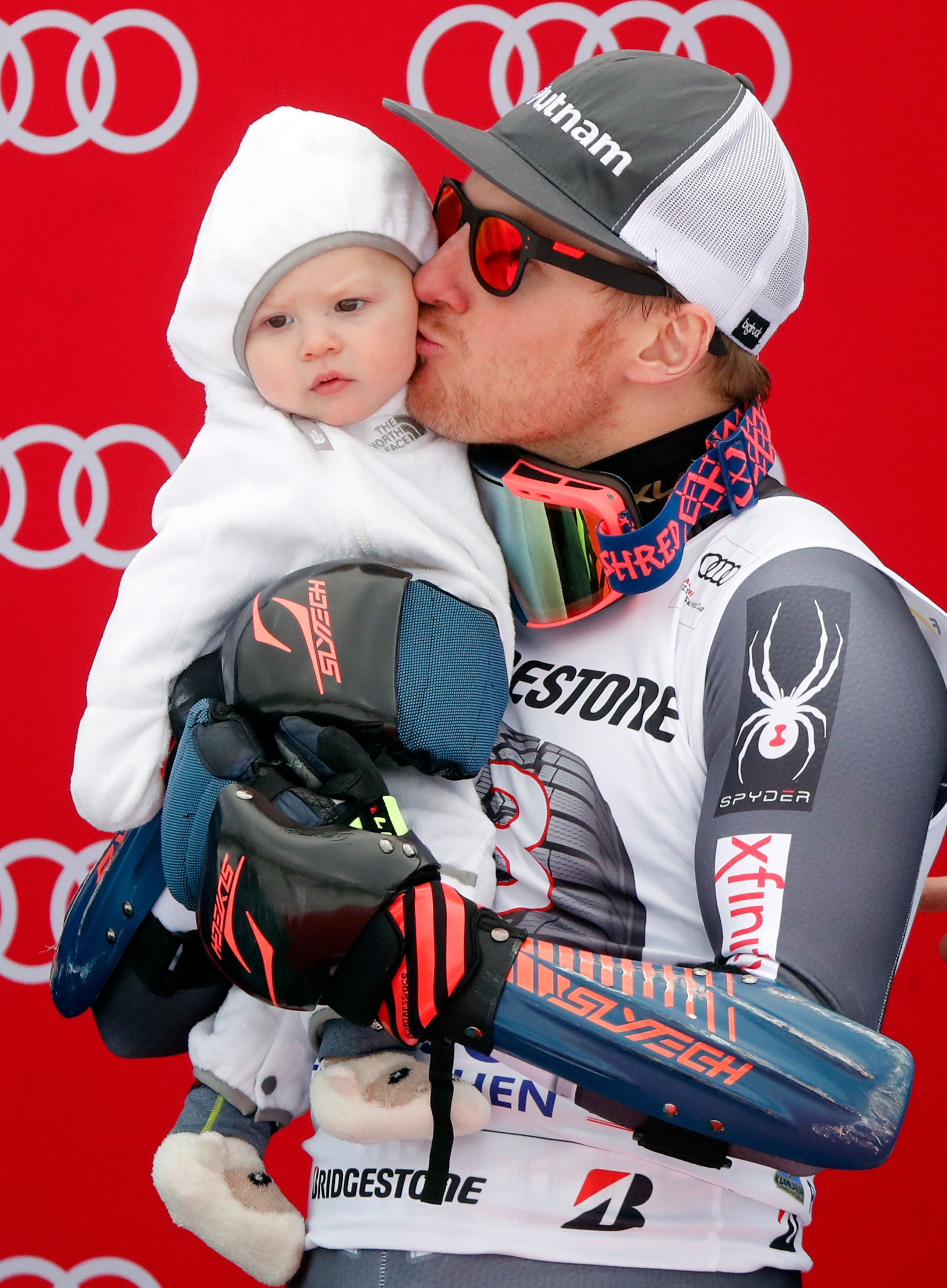 Alpine Skiing - FIS Alpine Skiing World Cup - Men's Giant Slalom - Garmisch-Partenkirchen, Germany - January 28, 2018 - Ted Ligety from the U.S. kisses his baby Jax on the podium. REUTERS/Wolfgang Rattay