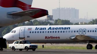 An Iranian Aseman Airlines' Fokker 100 prepares to take off as a British Airways aeroplane is seen in the foreground at Tehran's Mehrabad airport August 6, 2007. REUTERS/Morteza Nikoubazl (IRAN)