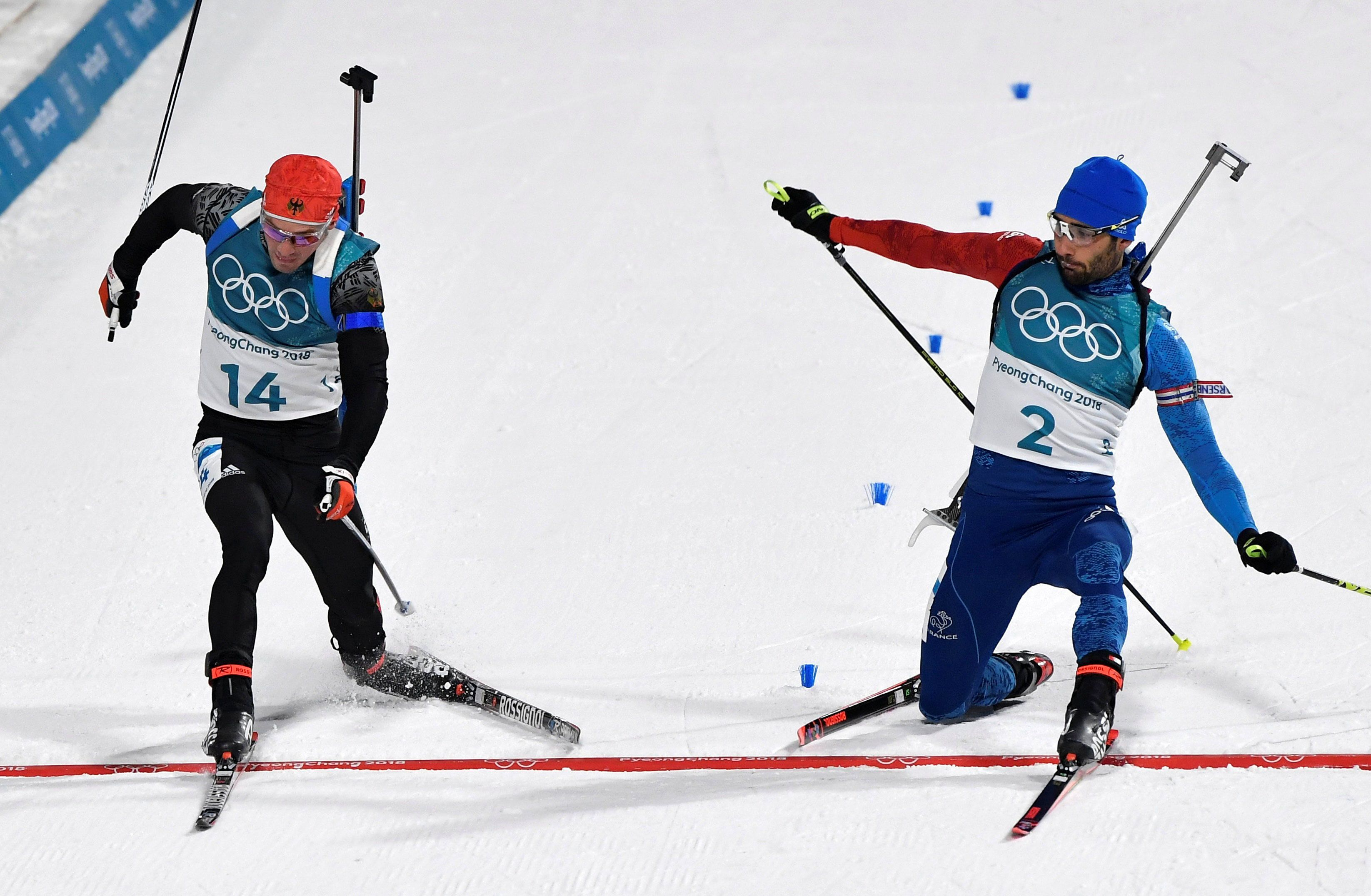 Simon Schempp of Germany, left, and Martin Fourcade of France, right, race to the finish line during...