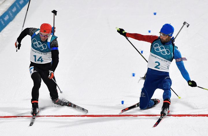 Simon Schempp of Germany, left, and Martin Fourcade of France, right, race to the finish line during Sunday'sMen's 15 km Mass Start Final.