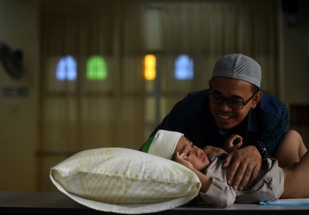 A four-year-old Muslim boy is comforted by his father before being circumcised during a ceremony at a...