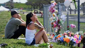 PARKLAND, FL - FEBRUARY 18: Angel Monge, left, and Stacey Sindon, center, wipe tears as people gather outside Marjory Stoneman Douglas High School on Sunday February 18, 2018 in Parkland, FL. A shooting on Wednesday at the school left 17 people dead. (Photo by Matt McClain/The Washington Post via Getty Images)