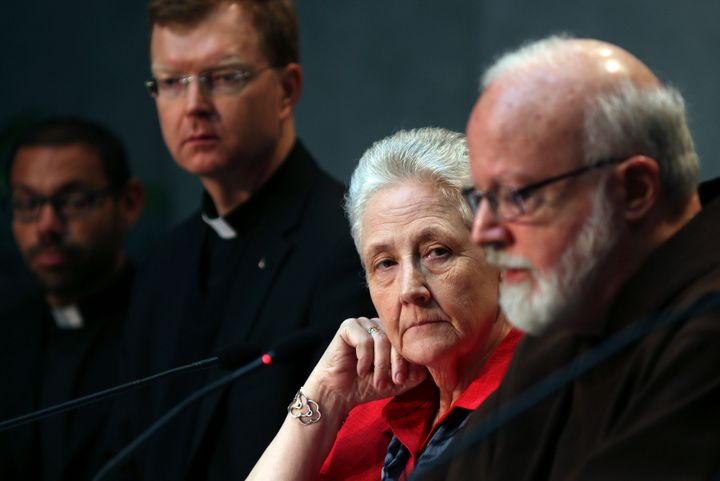 Marie Collins (second from right) watches as Cardinal Sean Patrick O'Malley (right) speaks during a briefing o