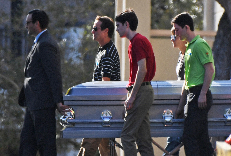 Pallbearers walk the casket of Scott Beigel, a teacher at Marjory Stoneman Douglas High School, following a service atT
