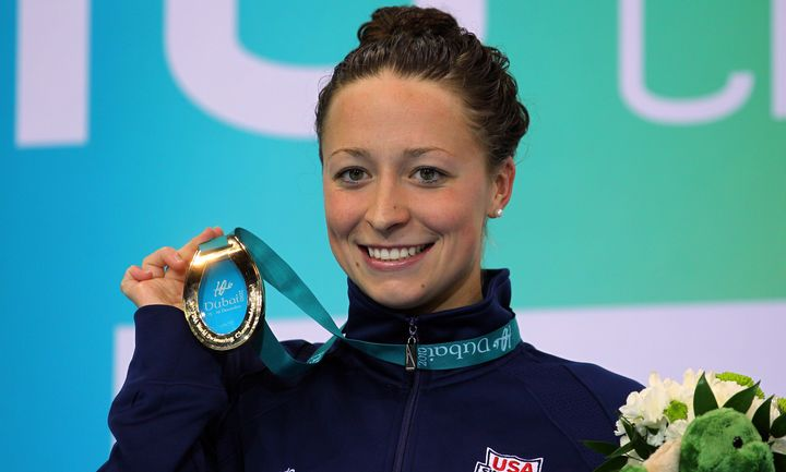 Ariana Kukorsholds up her gold medal after winning the women's 100-meter individual medley on day three of the World Sw