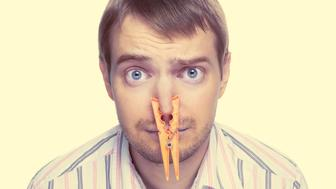 Portrait of caucasian man with orange clothespin on his nose - bad smell concept photography. Color toned image.