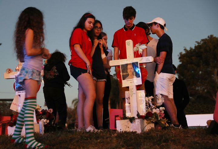 People visit a makeshift memorial at Marjory Stoneman Douglas High School on Sunday in Parkland, Florida, where 17 adults and
