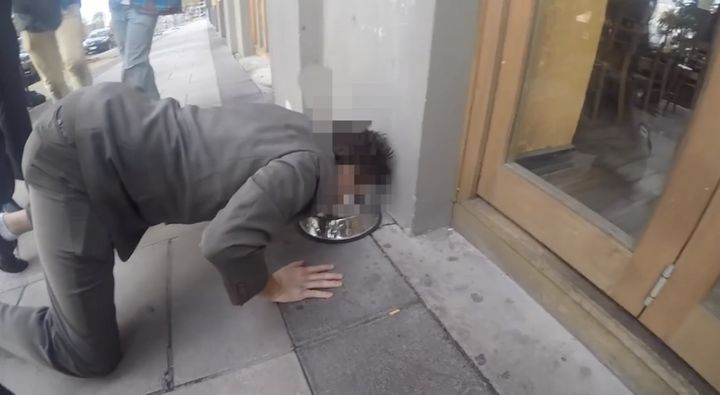 """A """"fresher"""" at the University of Newcastle in Australia drinks from a public dog bowl on a sidewalk."""