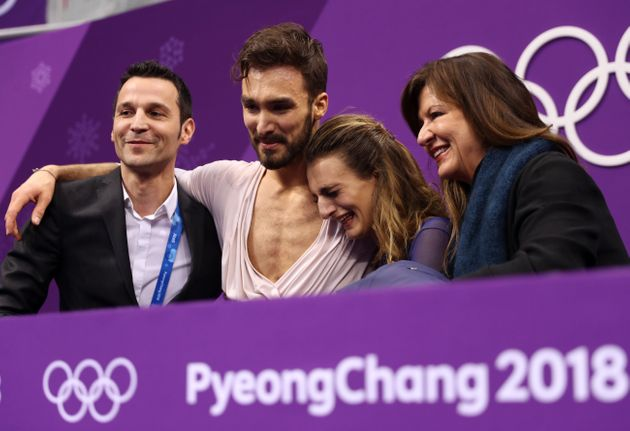 Gabriella Papadakis and Guillaume Cizeron, center, react after competing in the Figure Skating Ice Dance...