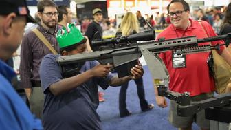 ATLANTA, GA - APRIL 29:  National Rifle Association members look over guns in the Barrett display at the 146th NRA Annual Meetings & Exhibits on April 29, 2017 in Atlanta, Georgia. With more than 800 exhibitors, the convention is the largest annual gathering for the NRA's more than 5 million members.  (Photo by Scott Olson/Getty Images)