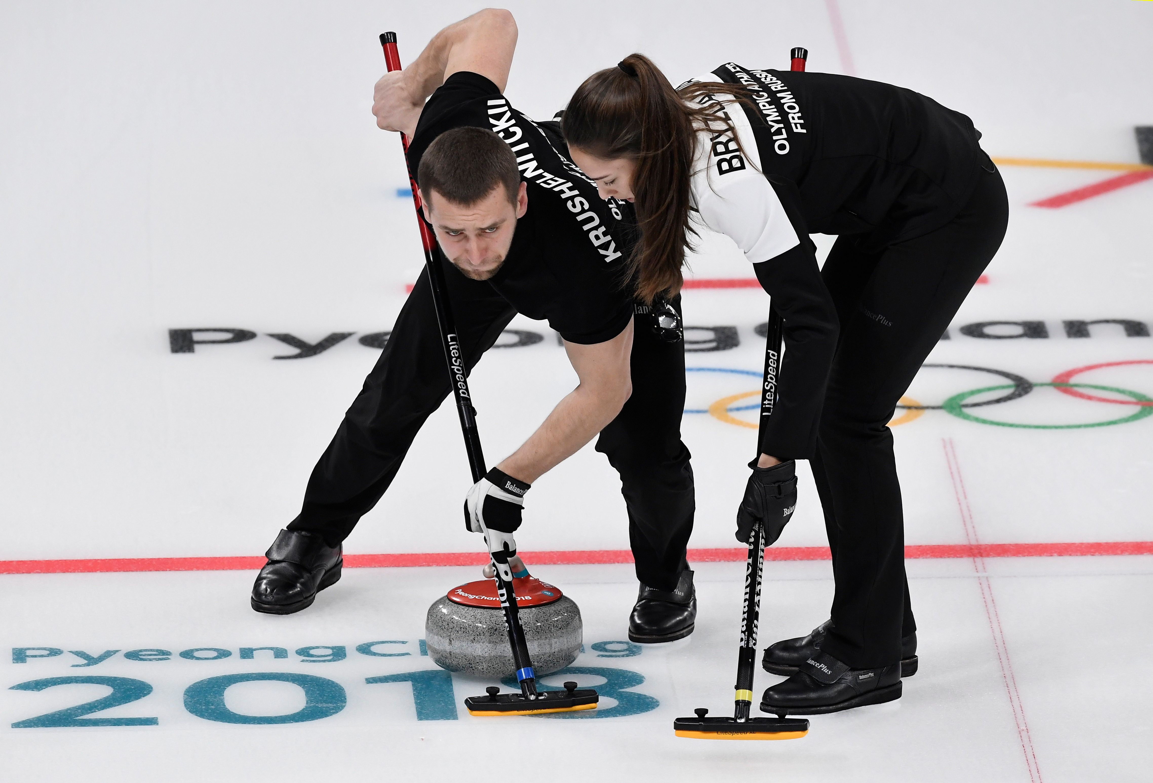 Curling – Pyeongchang 2018 Winter Olympics – Mixed Doubles Bronze Medal Match - Olympic Athletes from Russia v Norway - Gangneung Curling Center - Gangneung, South Korea – February 13, 2018 - Alexander Krushelnitsky and Anastasia Bryzgalova, Olympic athletes from Russia, sweep. REUTERS/Toby Melville