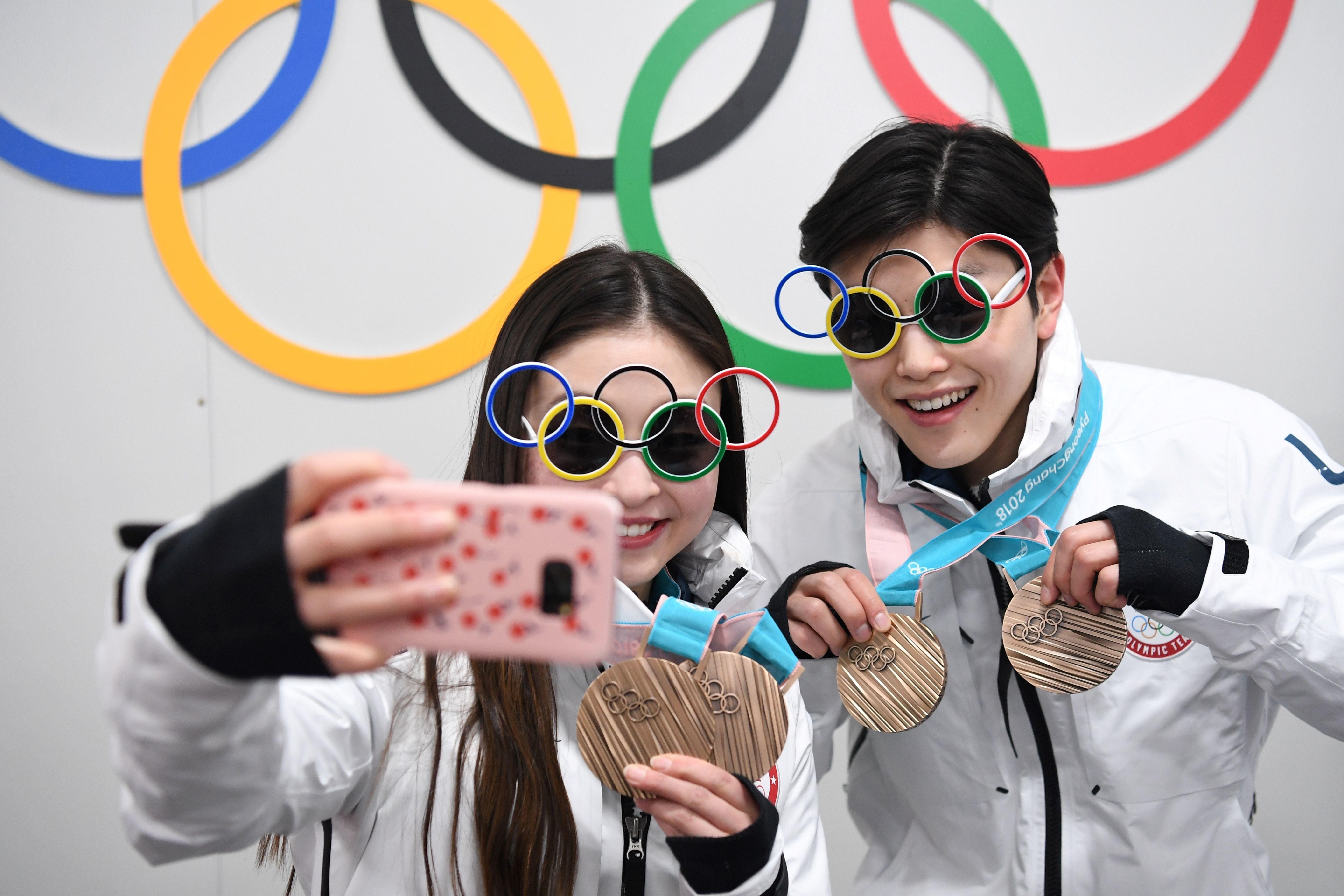 USA's figure skating bronze medallists Maia Shibutani and Alex Shibutani pose for a selfie in front of Olympic rings backstage at the Athletes' Lounge during the medal ceremonies at the Pyeongchang Medals Plaza during the Pyeongchang 2018 Winter Olympic Games in Pyeongchang on February 20, 2018. / AFP PHOTO / Dimitar DILKOFF        (Photo credit should read DIMITAR DILKOFF/AFP/Getty Images)