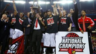 Louisville Cardinals head coach Rick Pitino holds up the trophy as he and his team celebrate after defeating the Michigan Wolverines in their NCAA men's Final Four championship basketball game in Atlanta, Georgia April 8, 2013. REUTERS/Jeff Haynes (UNITED STATES  - Tags: SPORT BASKETBALL TPX IMAGES OF THE DAY)
