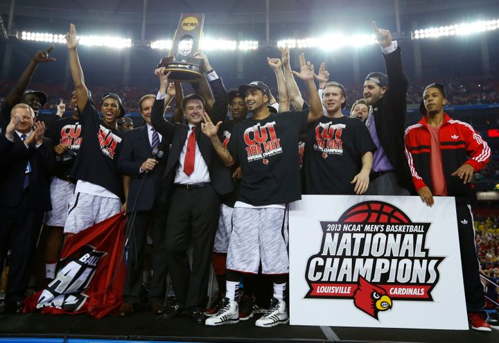 University of Louisville head basketball coach Rick Pitino hoists the trophy after his team defeated the University of Michig