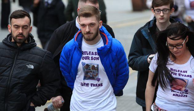 Tom Evans (centre) the partner of Kate James, the parents of 20-month-old son Alfie Evans, outside Liverpool...