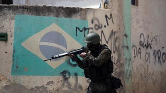 A Brazilian army soldier takes position in an alley during a security operation, at Barbante favela, where earlier in the week alleged drug traffickers destroyed a police post in Rio de Janeiro, Brazil on November 30, 2017.  / AFP PHOTO / LEO CORREA        (Photo credit should read LEO CORREA/AFP/Getty Images)