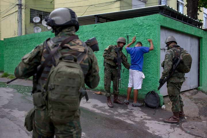 Brazilian army members stop and frisk a resident of the Cidade de Deus favela in Rio de Janeiro, during a security operation